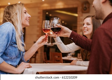 Young People In A Restaurant Cheering With Glasses Of Wine
