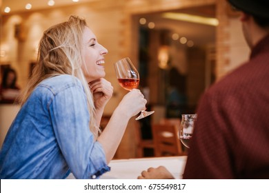 Young People In A Restaurant Talking And Drinking Wine