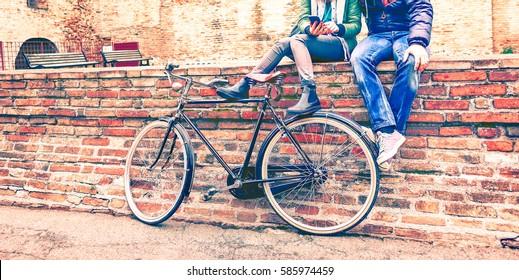 Junge Leute mit Retro-Fahrrad, die im Winter telefonisch an alten urbanen Wandschreibnachrichten sitzen - Mehrere der besten Freunde, die sich mit einem mobilen Cropp-Vintage-Filter umherbewegen, sehen die roten Töne mit erhöhter Farbe