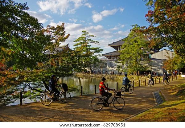 young people riding a bike in Todai-ji (Todaiji Temple) in Nara, under bright blue sky