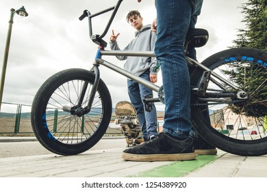 Young people riding bikes and skateboards in the city. Modern Guys with a skate and a bmx down the street.