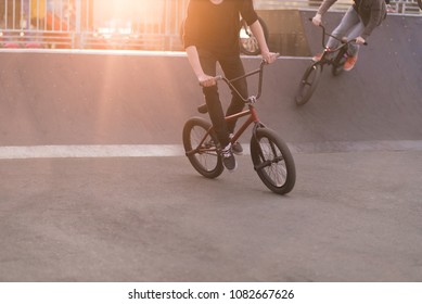 Young people riding a Bmx bike in a skate park in the background of the sunset. Bmx Concept. Bmx Bicycle Training