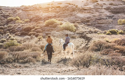 Young people riding horses doing excursion at sunset - Wild couple having fun in equestrian tour  - Training, culture, passion, healthy lifestyle, sport concept