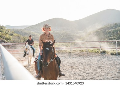 Young people riding horses inside corral - Wild couple having fun in equestrian ranch  - Training, culture, passion, excursion, healthy lifestyle, sport concept - Focus on woman face
