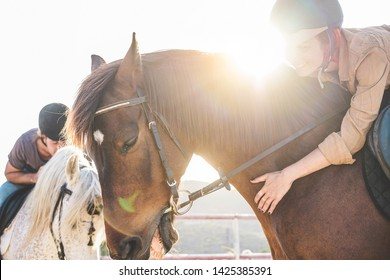 Young people riding and taking care of horses inside corral - Happy couple having fun in equestrian ranch  - Training, culture, passion, excursion, sport concept - Focus on woman hand