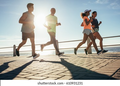 Young people running along seaside on a sunny day. Group of runners working out on a road by the sea.
