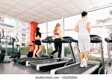 Young people running on treadmills in gym