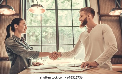 Young people shake hands at the conclusion of a business deal in an office