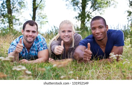 Young people showing thumbs up while lying on wild meadow.