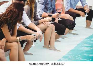 Young people sitting by swimming pool, drinking, having fun, enjoying holiday