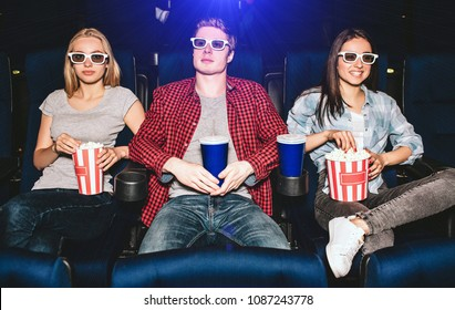 Young people are sitting in chairs in cinema. They wear glasses for watching movies. Guy has cup of coke while girls have basket of popcorn. They are watching movie. Blonde girl is looking on camera.