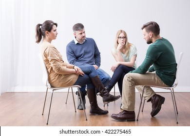 Young people sitting in circle during psychotherapy session
