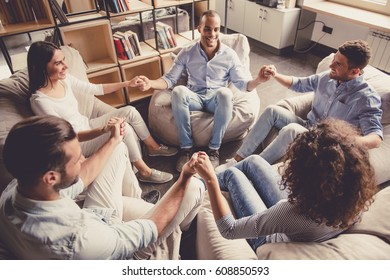Young people are sitting in circle, holding hands and smiling