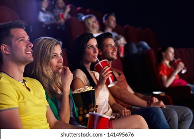 Young people sitting in multiplex movie theater, watching movie, eating popcorn.