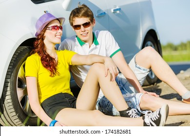 Young people sitting near car aside of road