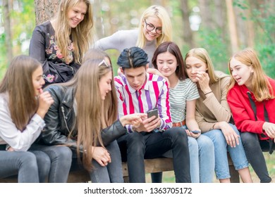Young people sitting on a bench in the woods and look at the phone. Summer day