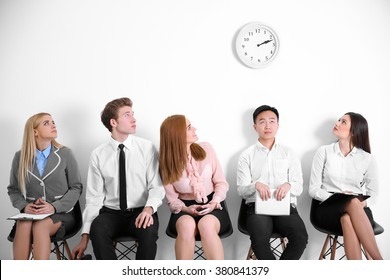 Young people sitting on a chairs and looking at the clock in white hall