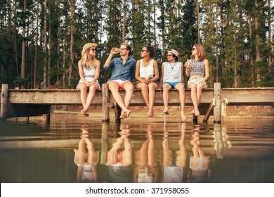 Young people sitting on the edge of a jetty with their hanging down to the water. Group of young friends hanging out at the lake.