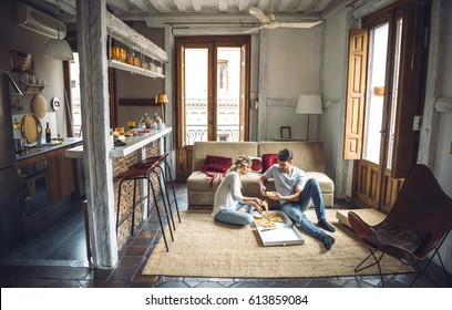 Young people sitting on floor in living room and eating ordered pizza.