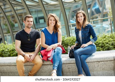 Young people sitting on the street, smiling happy, looking at camera.