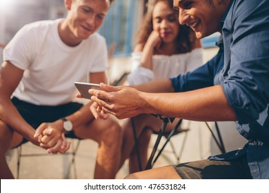 Young people sitting outdoors and looking at mobile phone. Group of friends sitting at outdoor cafe and watching video on the smartphone.