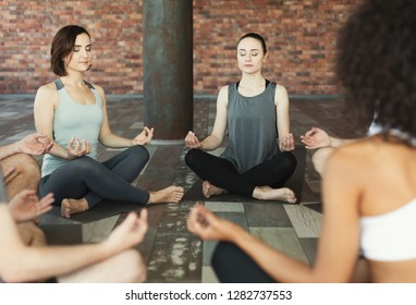 Young people sitting in Sukhasana pose on mats in circle doing breathing practice, yoga studio in loft.