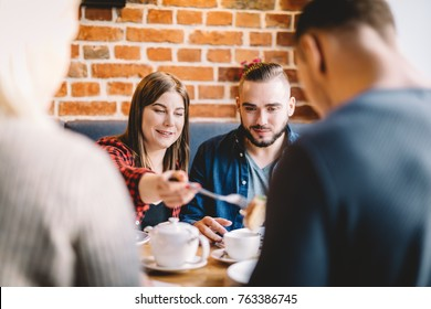 Young people sitting at the table in a restaurant. Girl is taking a piece of food from a man sitting across her.