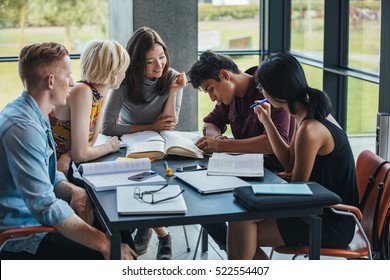 Young people sitting at table working on school assignment. Multiracial group of students studying together in a library.