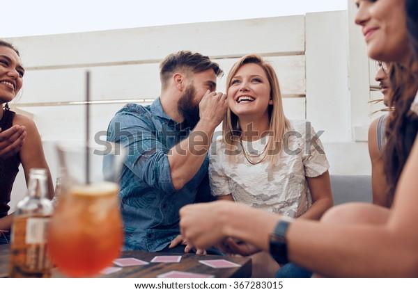 Junge Leute sitzen zusammen auf einer Party. Mann flüstert etwas in den Ohren der Frau. Teilen eines Geheimnisses.