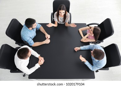 Young people sitting together at table, indoors. Unity concept