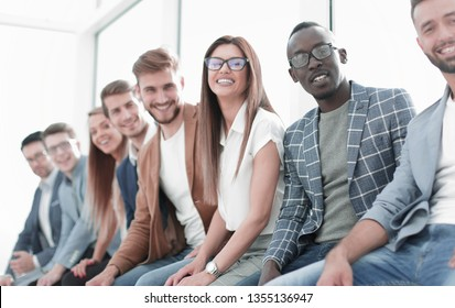 young people sitting at the wall waiting for their turn at the interview