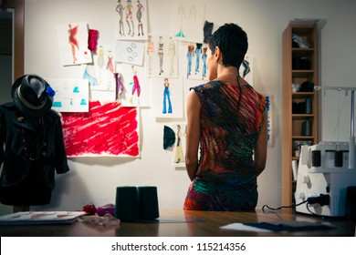 Young people and small business, hispanic woman at work as fashion designer and tailor, looking at sketches of new collection in atelier