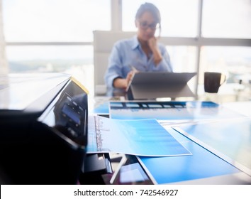 Young people, small business, technology. Woman working as photographer in studio. Girl with computer laptop for photo editing. Close-up of printer printing picture on photographic paper