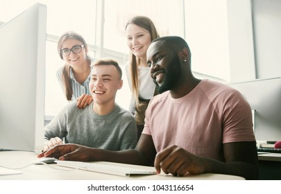 Young people smiling, sitting at table and using computer in  light office.