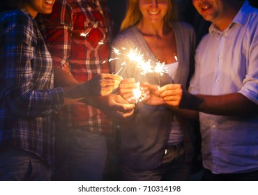 Young people with sparklers having fun on night outdoor party