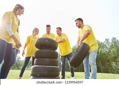 Young people are stacking car tires in teamwork event at a teambuilding event