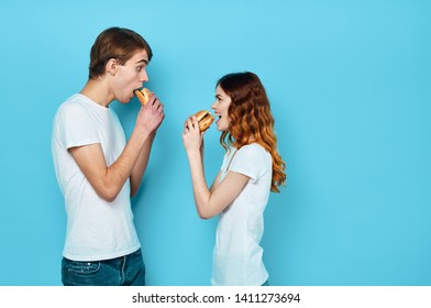 Young people stand in front of each other and eat hamburgers