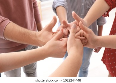 Young people standing in circle and showing thumb-up gesture as symbol of unity