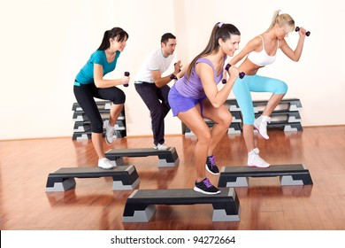 young people stepping with dumbbells in gym