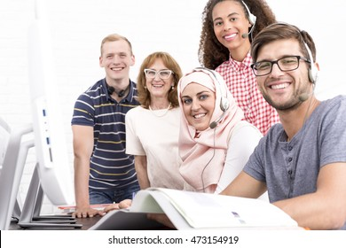 Young people from students exchange program and mature IT teacher