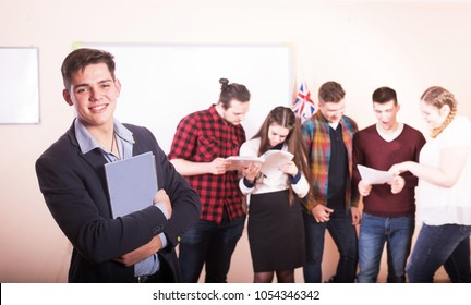 Young people studying with books on white desk. Beautiful girls and guys working together wearing casual clothes.