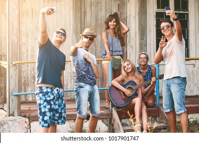 Young people take selfie with their smartphones while hanging out with friends and playing guitar at the summer wooden cabin