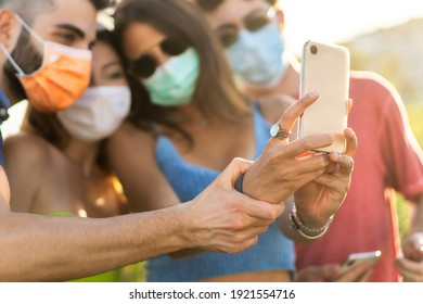 Young people taking selfie using a cellphone wearing face masks. Group of young people photographing themselves with the coronavirus masks. New normal lifestyle concept. Focus on the smartphone.