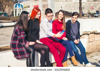 young people taking selfies in city