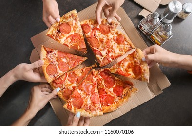 Young people taking slices of delicious pizza from cardboard box on table