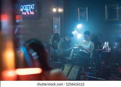 Young people in tattoo studio. Persons in beauty parlor and fashion salon for modern tattooing and body art. Two girls getting tattoos on arm skin by professional tattooists. Shot through a mirror.