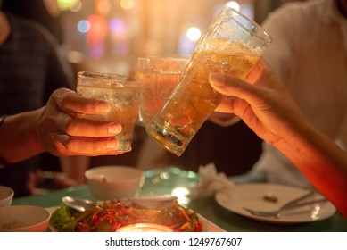Young People toasting and cheer beer glasses,drink at bar party.Happy hour or chill out time,group of friends drunk from beverage(beer,wine,coctail)