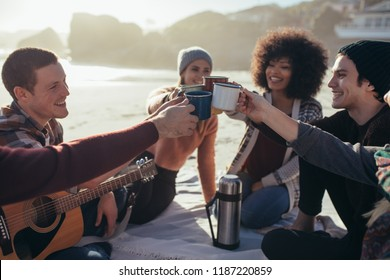 Young people toasting with coffee cups on beach. Group of men and women having coffee together at sea shore.