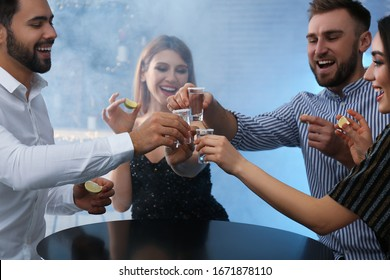 Young people toasting with Mexican Tequila shots at table in bar