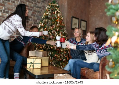 Young people toasting with mulled wine while celebrating Christmas near decorated Christmas tree in cozy loft